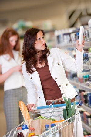 woman shopping cart: Young woman buying shampoo