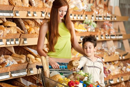 Red hair woman with little boy buying bread Stock Photo