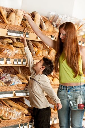 Red hair woman and child choosing bread in a supermarket photo
