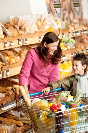 Shopping series - Woman with child in winter outfit in a supermarket Stock Photo