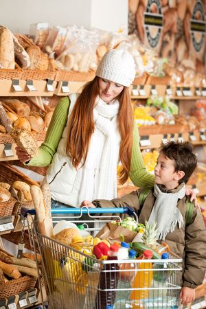 woman shopping cart: Shopping series - Red hair woman with child choosing bread