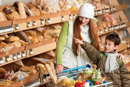 Shopping series - Red hair woman with little boy choosing bread photo