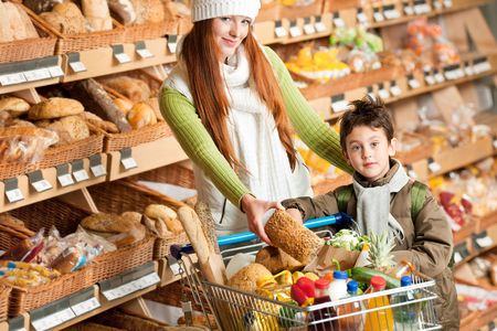 Shopping series - Happy woman with child choosing bread photo