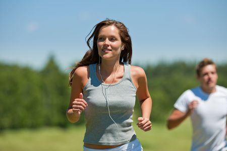woman running: Brown hair woman with headphones jogging, man in background, shallow DOF