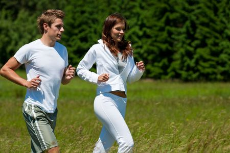 Young man and woman running outdoors on a sunny day, shallow DOF photo