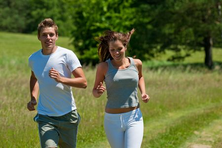 Young man and woman running outdoors, shallow DOF photo