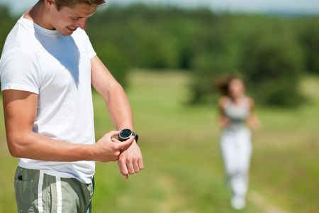 Young man with stopwatch measuring time, woman in background, shallow DOF photo