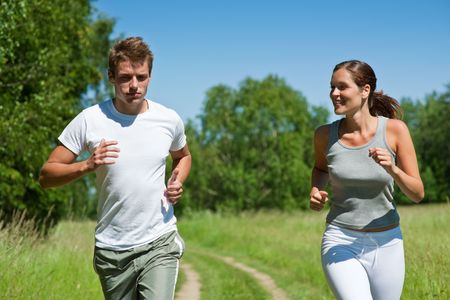 sportive: Sportive man and woman jogging outdoors, shallow DOF