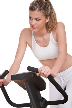 Fitness series - Young woman on exercise bike on white background photo