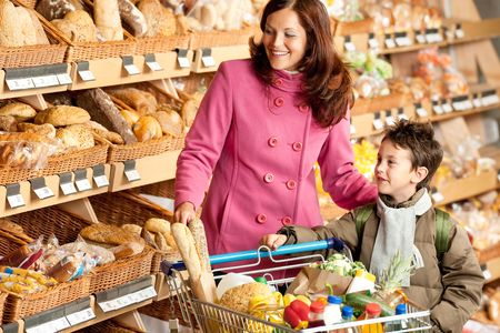 supermarket cart: Shopping series - Smiling woman with child in a supermarket Stock Photo