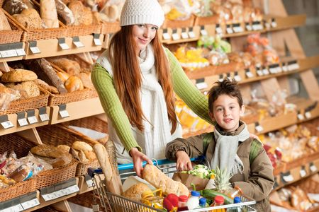 Shopping series - Long red hair woman with little boy in a supermarket photo