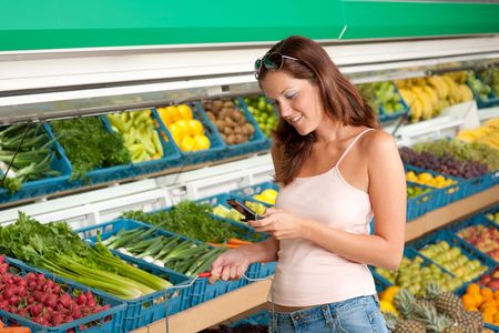 supermarket series: Shopping series - Woman holding mobile phone in a supermarket Stock Photo