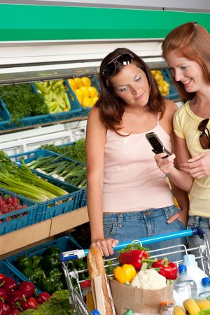 grocery store series: Shopping series - Two women with mobile phone in a grocery store Stock Photo