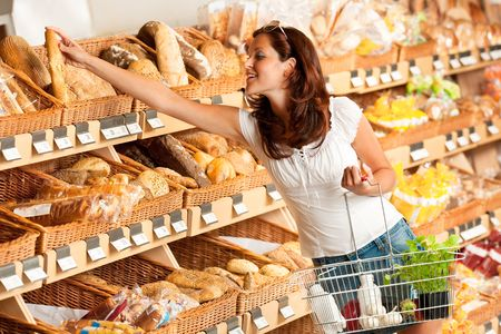 Grocery store: Young woman holding shopping basket and choosing bread photo