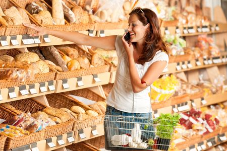 grocery stores: Grocery store: Young woman holding mobile phone and shopping basket
