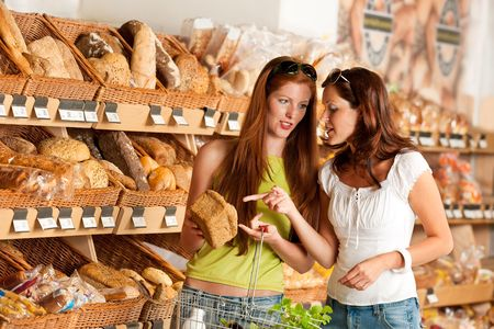Grocery store: Two women choosing bread at bakery photo