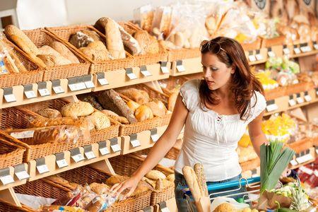 bread shop: Negozio: giovane donna con il carrello della spesa e la scelta di pane
