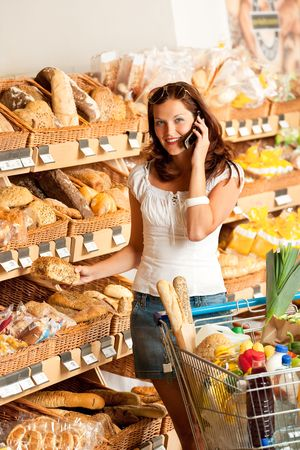 Grocery store: Young woman with mobile phone and shopping cart photo