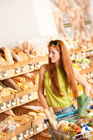 Grocery store: Red hair woman with shopping cart at bakery photo