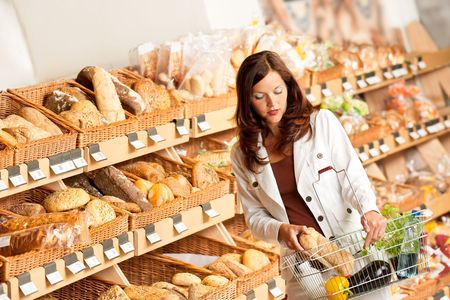 Grocery store: Young woman buying bread at bakery photo