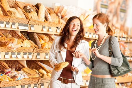 clothing stores: Grocery store: Two women choosing bread and having fun