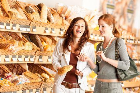 canasta de panes: Tienda de comestibles: Dos mujeres que eligen el pan y la diversi�n