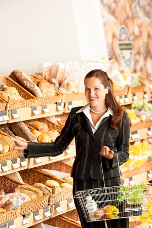 Grocery store: Business woman choosing bread in a supermarket photo