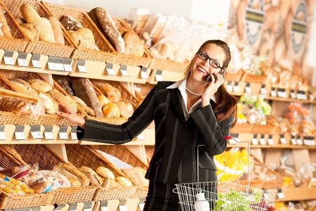 Grocery store: Business woman with mobile phone in a supermarket photo