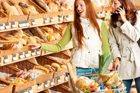 Grocery store: Red hair woman and brunette in winter outfit choosing bread photo