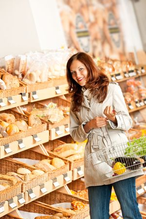 Grocery store: Young woman in bakery department holding shopping basket photo
