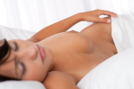 Brown hair woman sleeping naked in white bed, focus on nipple, shallow DOF Stock Photo - 5306927
