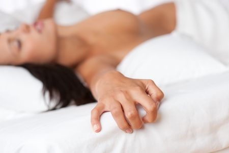 Naked woman lying in bed, focus on hand, shallow DOF