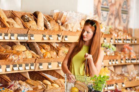 canasta de panes: Tienda de comestibles: pelo rojo mujer de compras en un supermercado Foto de archivo