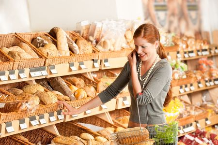 Grocery store: Red hair woman with mobile phone in a supermarket Stock Photo - 5313896