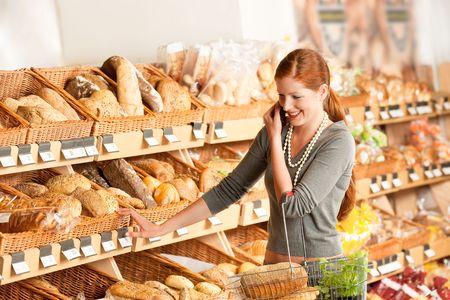 canasta de panes: Tienda de comestibles: mujer con el cabello rojo de tel�fono m�vil en un supermercado