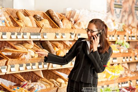 Grocery store: Young business woman holding mobile phone and shopping basket photo