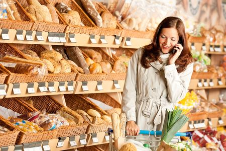 Grocery store: Young brown hair woman with mobile phone and shopping cart photo