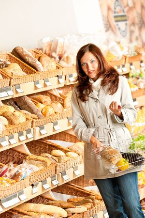 Grocery store: Young woman with shopping basket in a supermarket photo