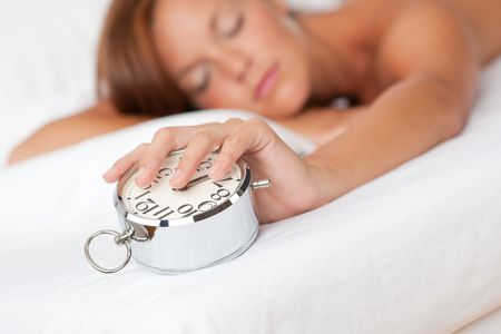 Woman holding silver alarm clock, shallow DOF photo