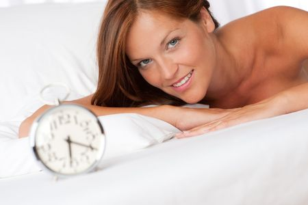 Young woman lying in bed, alarm clock in foreground photo