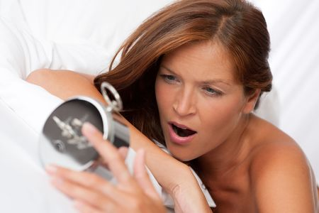 Brown hair woman yawning and holding alarm clock in white bed photo