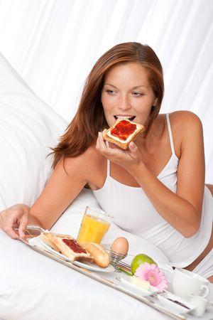 luxury hotel room: Young woman having breakfast in luxury hotel room Stock Photo