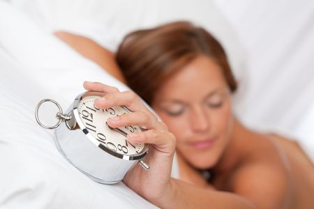 Beautiful sleeping woman holding alarm clock in white bed photo
