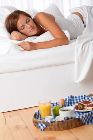 Young woman having home made breakfast in bed, sleeping Stock Photo