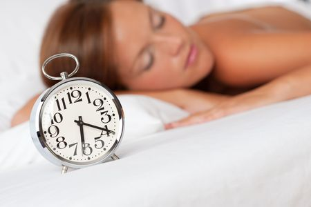 Silver alarm clock on white bed woman in background photo