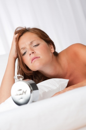 Tired woman watching alarm clock in white bed Stock Photo - 5383805