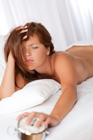 Tired woman holding silver alarm clock lying on white bed photo