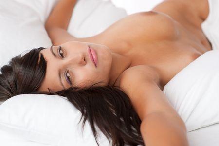mujer sexy desnuda: Sexy joven desnudo acostado en la cama de color blanco, someras DOF Foto de archivo