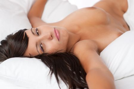 Sexy  woman naked: Sexy young woman lying naked in white bed, shallow DOF