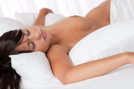 Naked woman sleeping in white bed, shallow DOF photo